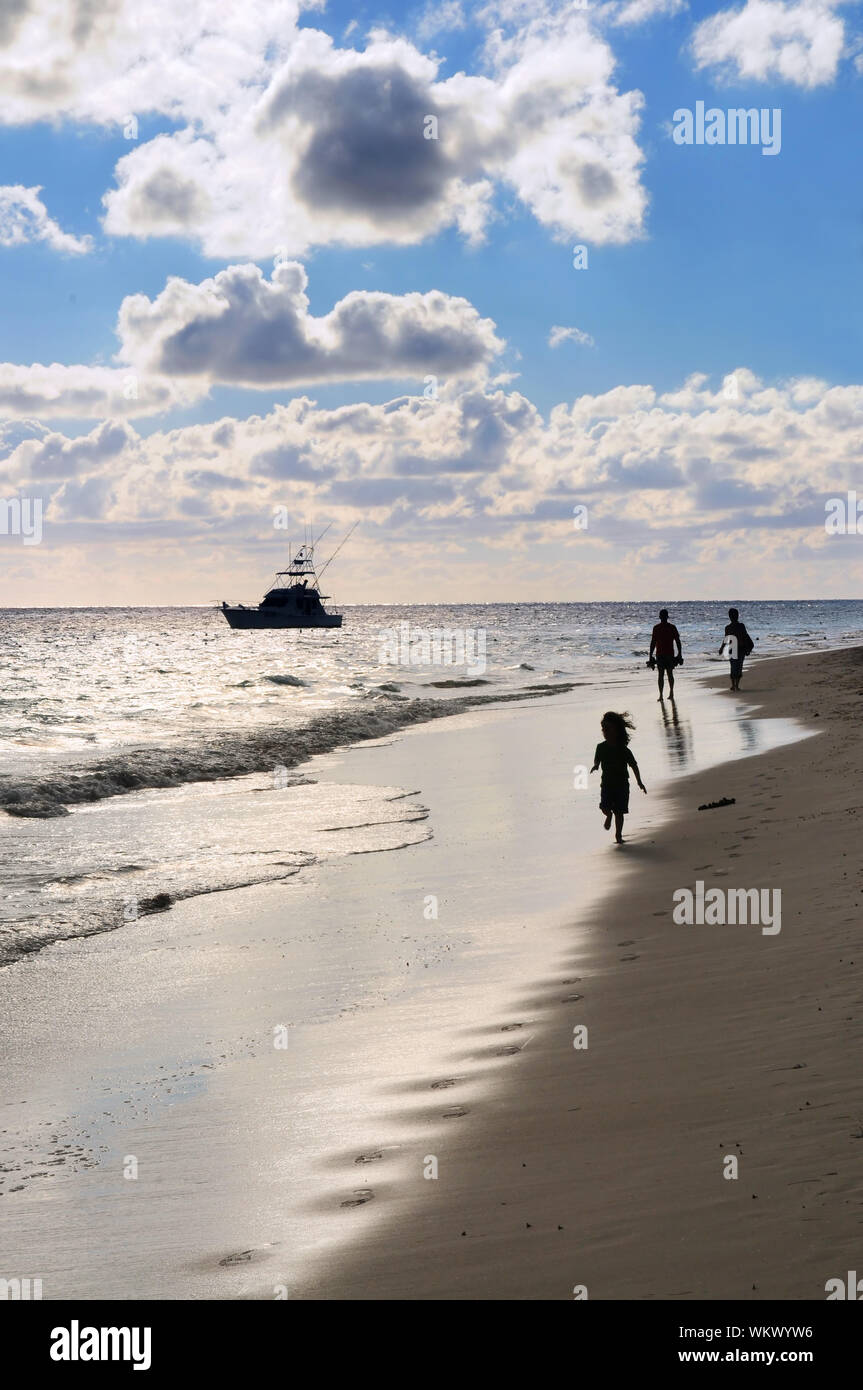 Family Taking A Walk On A Sandy Beach Of Tropical Resort At