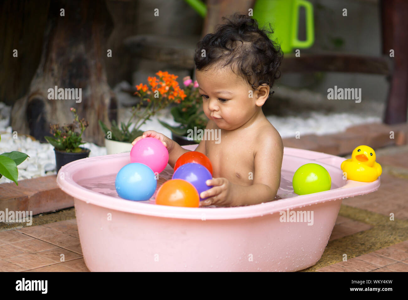 Shirtless Baby Boy Playing With Colorful Balls In Bathtub Stock Photo