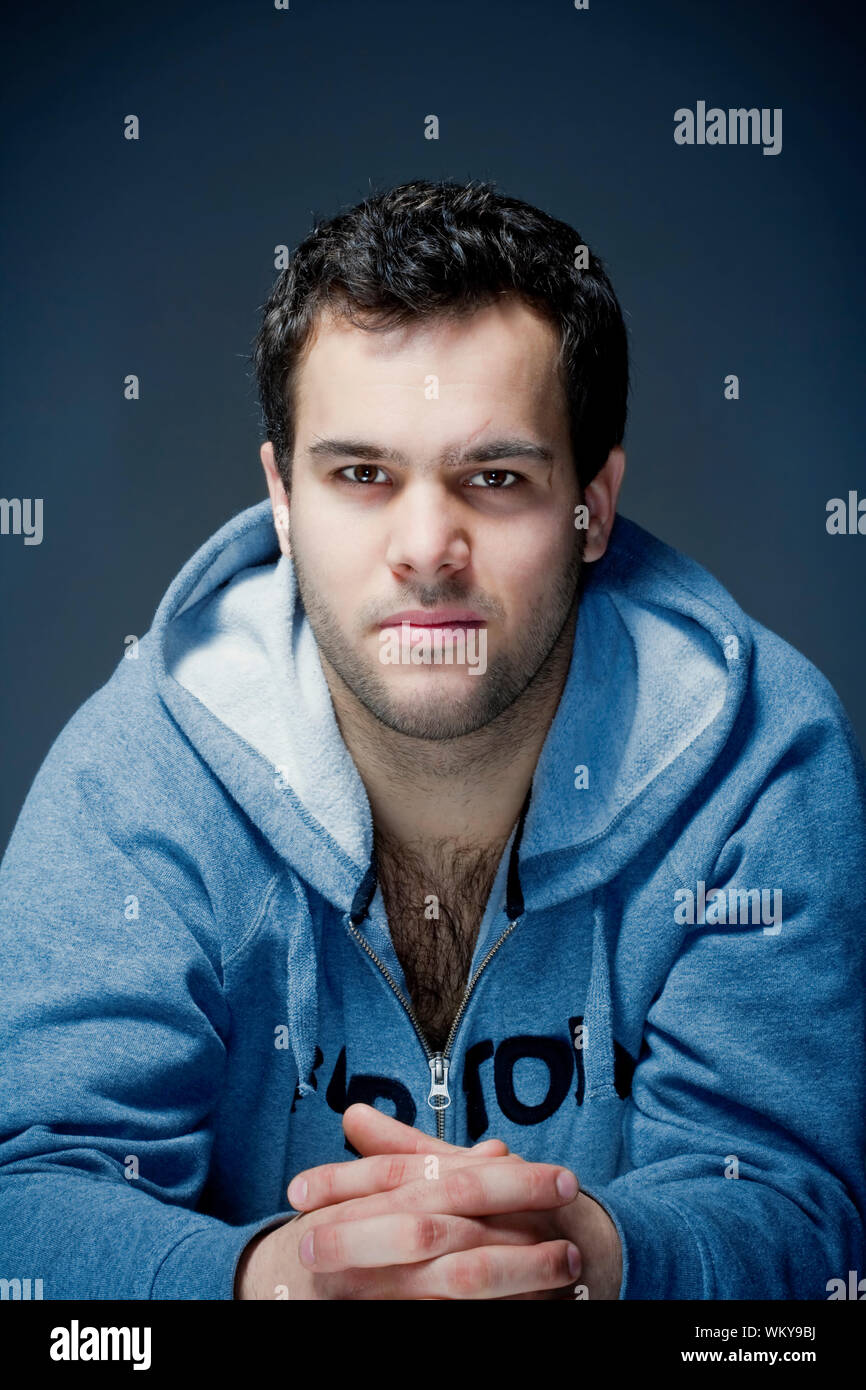 Portrait Of A Young Tough Man With Dark Hair Isolated On Dark Blue Stock Photo Alamy