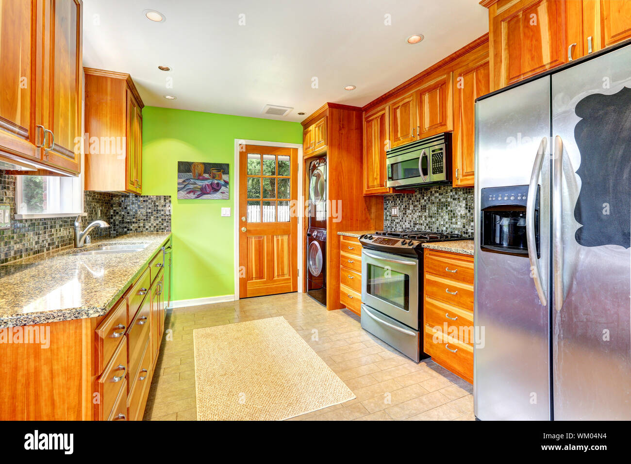 Maple Kitchen Cabinets With Mosaic Back Splash Trim And Granite Tops Bright Kitchen Room With Green Wall Stock Photo Alamy