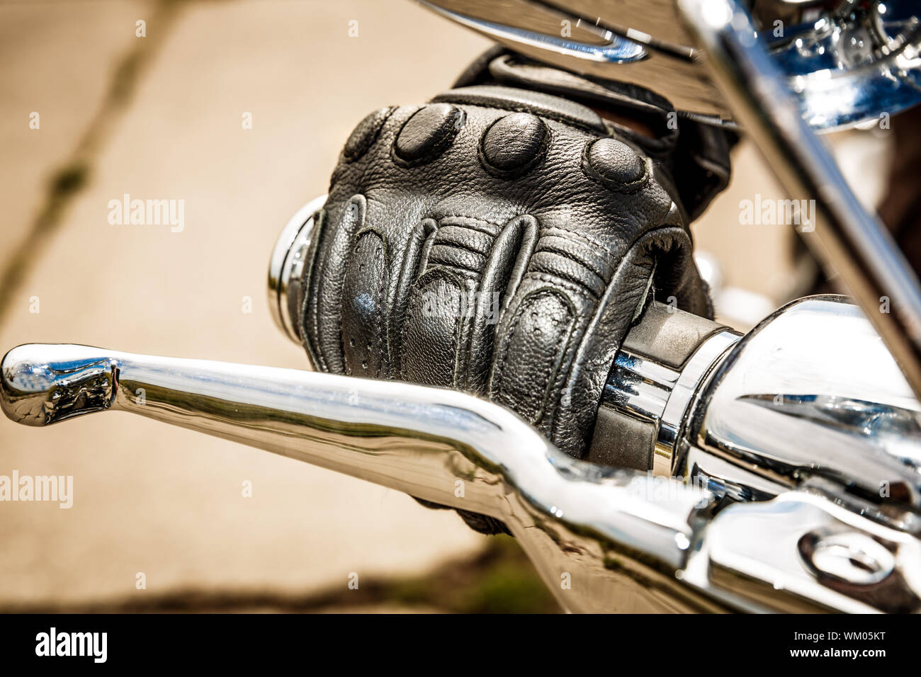 Human hand in a Motorcycle Racing Gloves holds a motorcycle throttle control. Hand protection from falls and accidents. Stock Photo