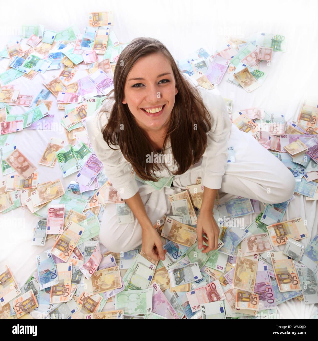 Junge Frau sitzt glücklich im Geld. Sie sitzt auf vielen Euro-scheinen. Stock Photo