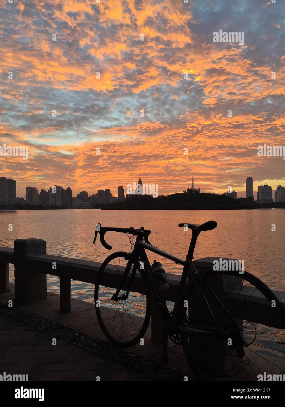 Bicycle Parked On Railing By Lake Against Cloudy Sky During Sunset Stock Photo