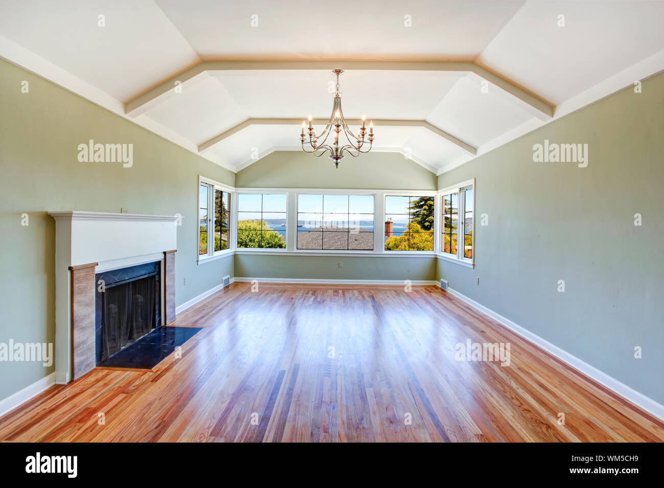 Empty specious living room interior with vaulted ceiling, light mint walls, hardwood floor and fireplace. Room with bay view Stock Photo