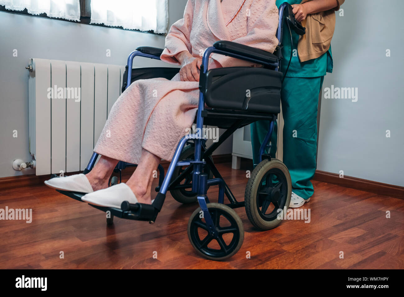 Nurse With Senior Patient On Wheelchair In Hospital Ward Stock Photo