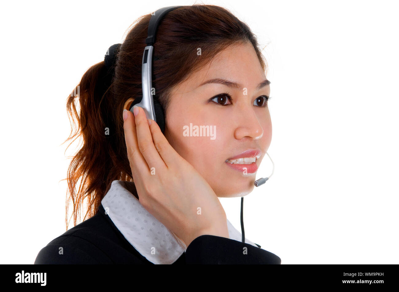 Friendly Customer Representative with headset smiling during a telephone conversation. Stock Photo