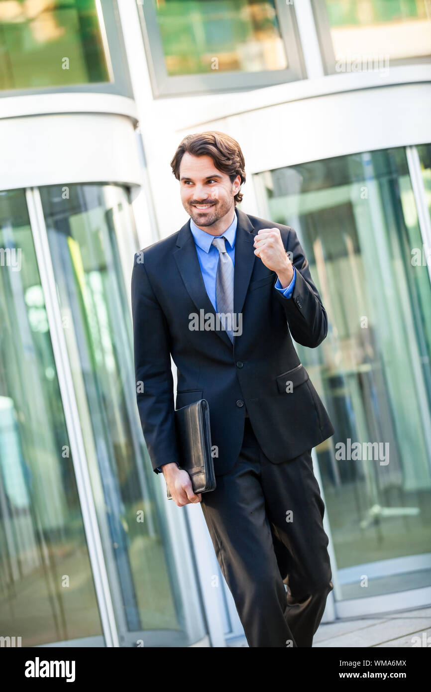 Motivated handsome young businessman leaving his office building with a briefcase under his arm punching the air with his fist and smiling after a suc Stock Photo