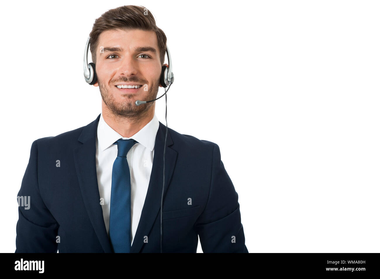 Young bearded handsome man wearing formal business suit and headset with stereo headphones and microphone while smiling at camera, portrait on white Stock Photo