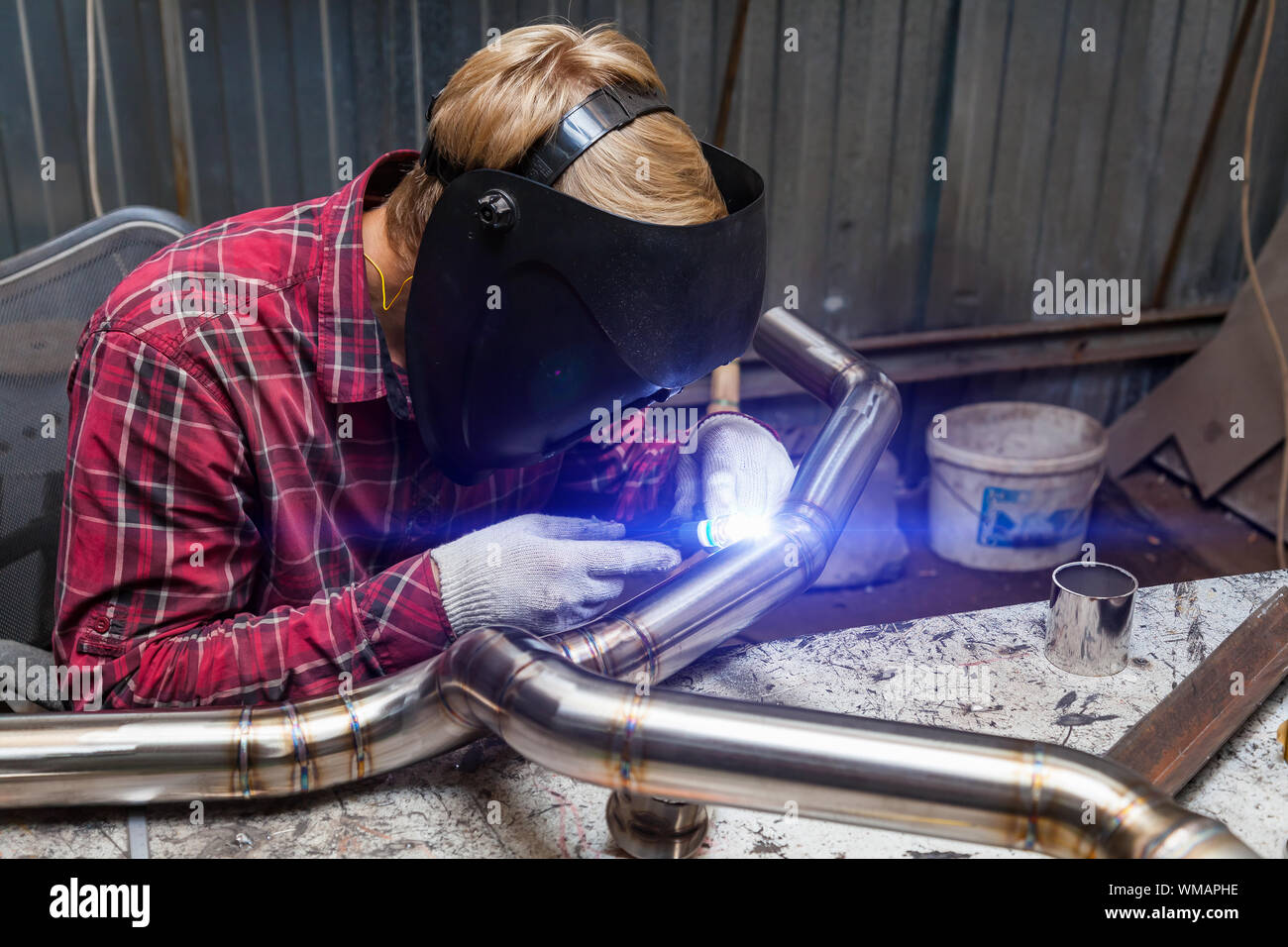 Young Guy Welder In A Checkered Red Shirt Welds A Stainless Steel Pipe For Car Exhaust Using Agronomic Welding To Protect His Eyes With A Mask In An I Stock Photo