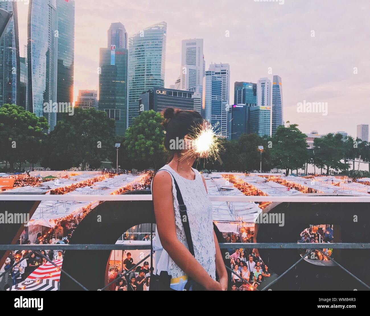 Digital Composite Image Of Firework Exploding On Woman Face In City During Event Stock Photo
