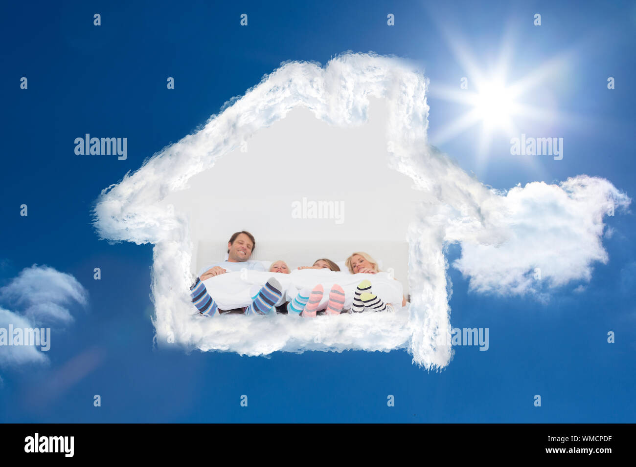 Family wearing stripey socks against bright blue sky with clouds Stock Photo