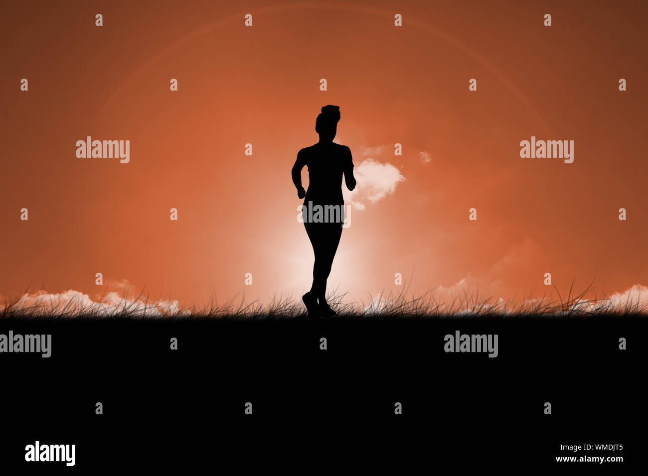 Fit brunette jogging away from camera against sun set Stock Photo
