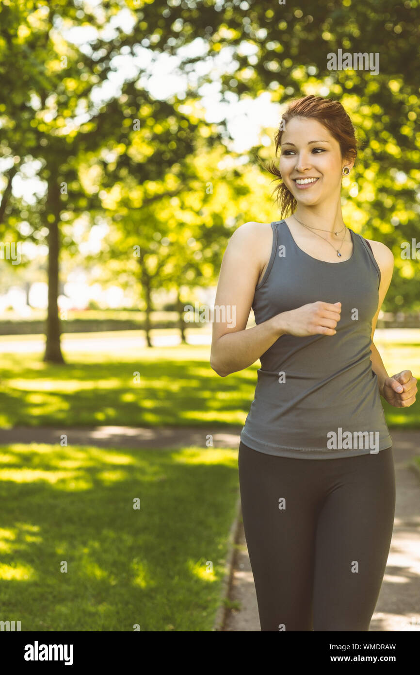 Portrait of a pretty redhead running on a sunny day Stock Photo
