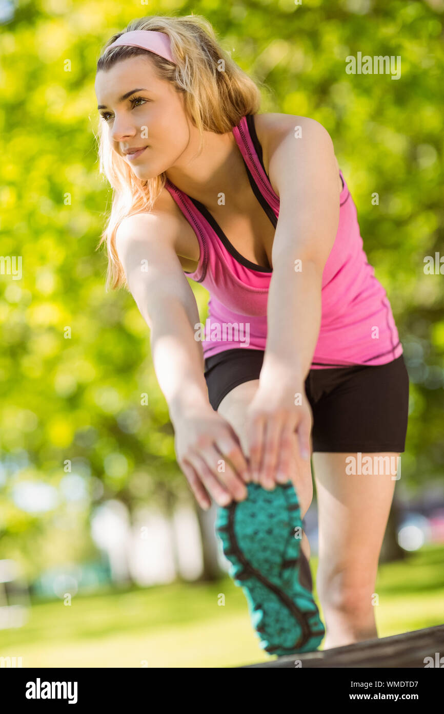 Fit blonde stretching her leg on a sunny day Stock Photo