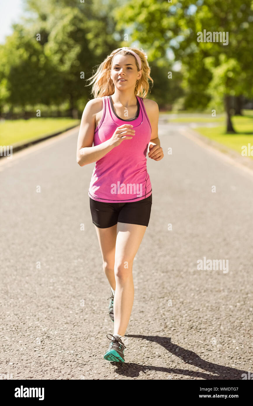 Fit blonde jogging in the park on a sunny day Stock Photo