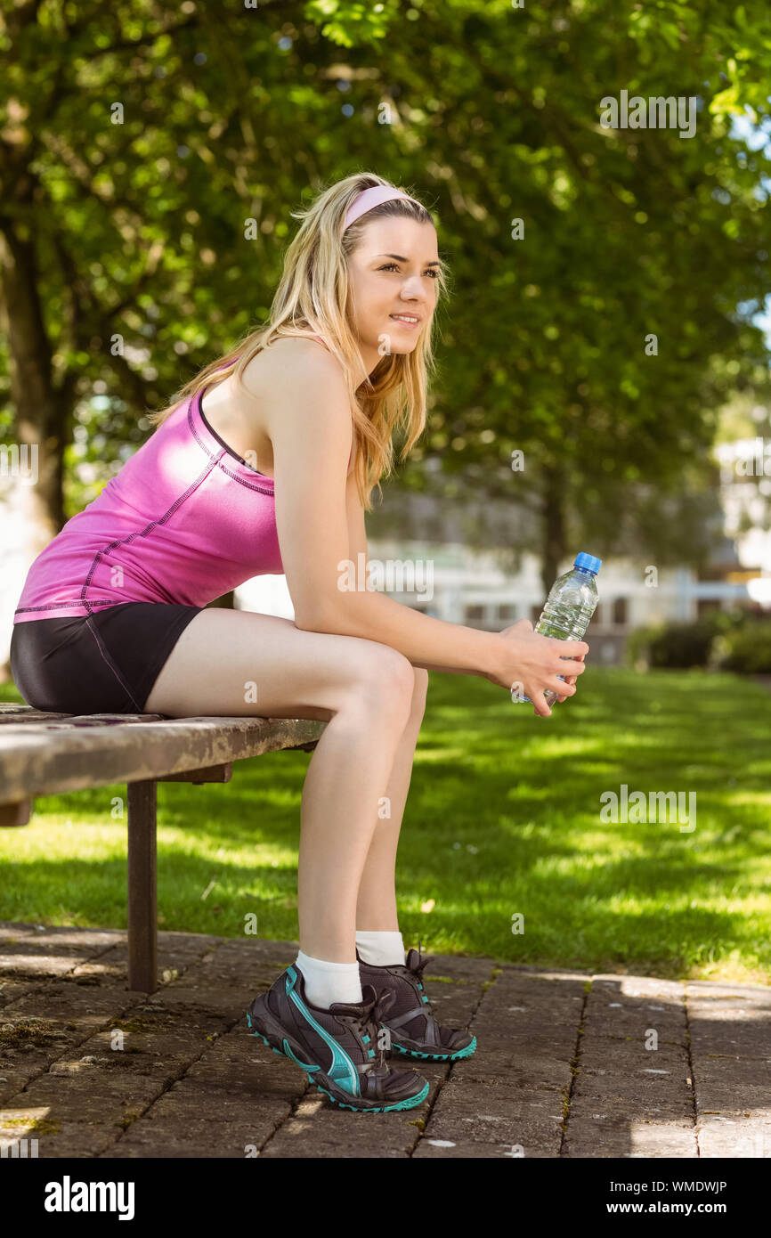 Fit blonde taking a break in the park on a sunny day Stock Photo
