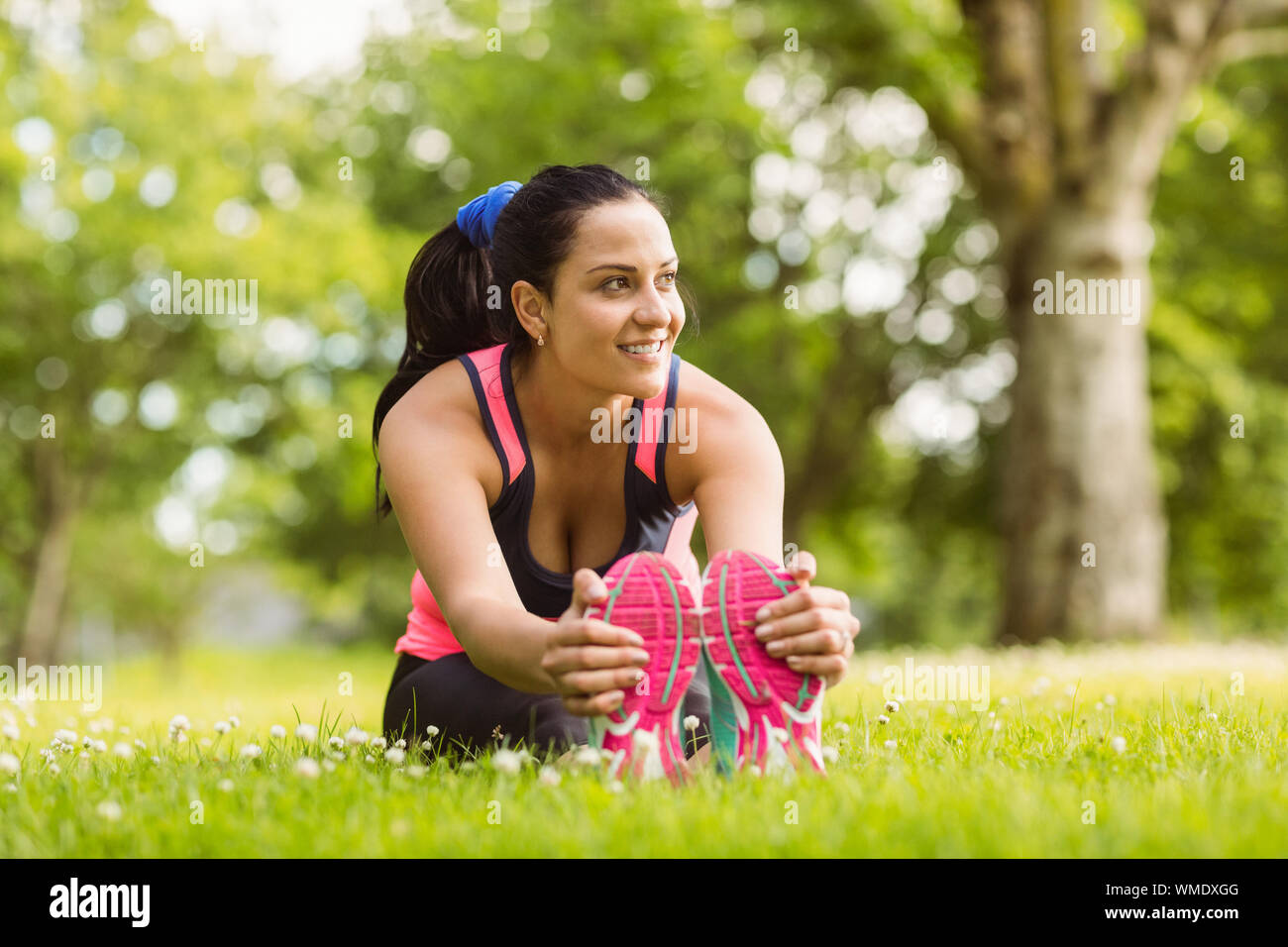 Fit brown hair stretching on the grass in the park Stock Photo