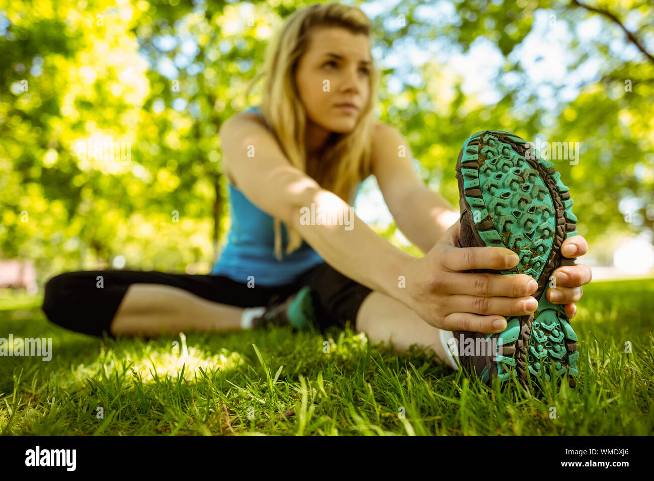 Fit blonde stretching on the grass on a sunny day Stock Photo