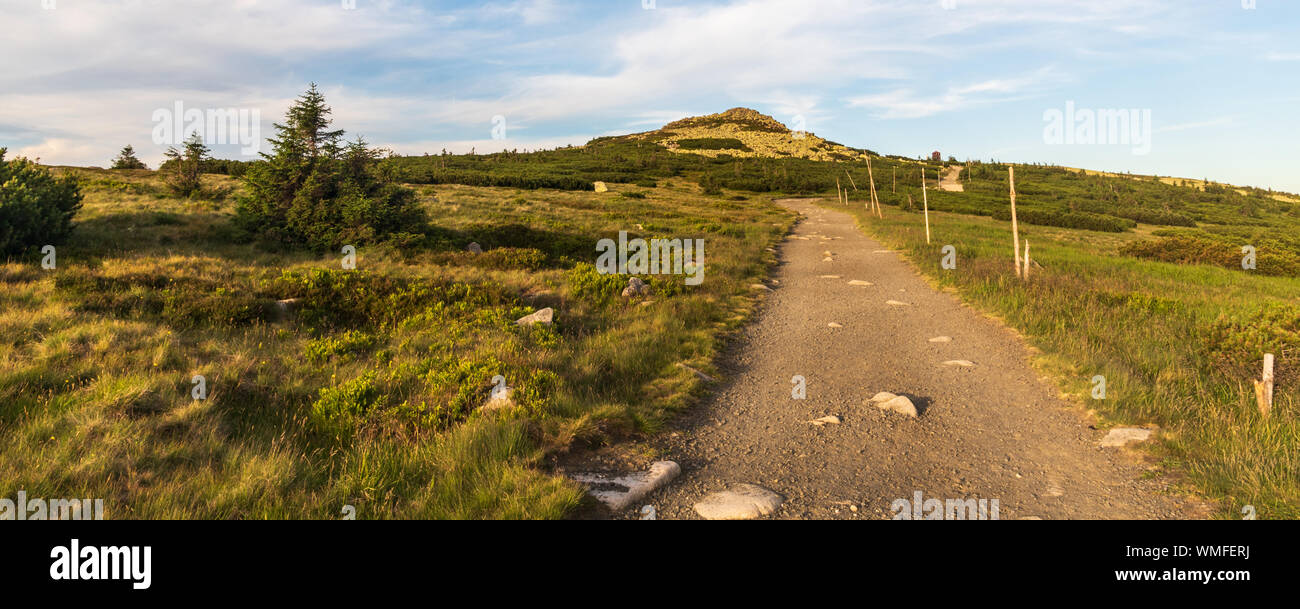 Rocky Violik hill with hiking trail and building on Snezne jamy on the background in evening Krkonose mountains on czech-polish borders Stock Photo