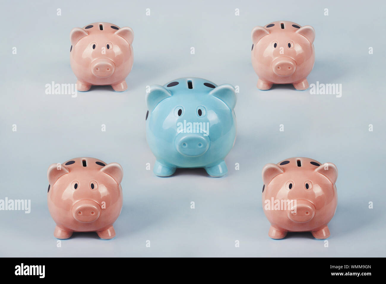 Different colored piggy bank standing out of the crowd. The uniqueness and leadership concept, individuality and difference. Finance and money saving Stock Photo