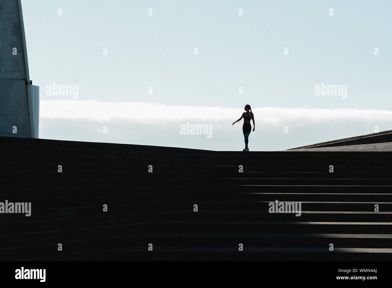 Silhouette of woman walking on stairs with blue sky in background Stock Photo
