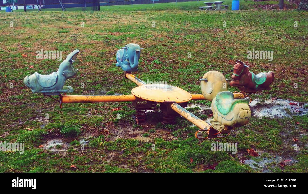 Abandoned Playground Equipment On Field In Park Stock Photo Alamy