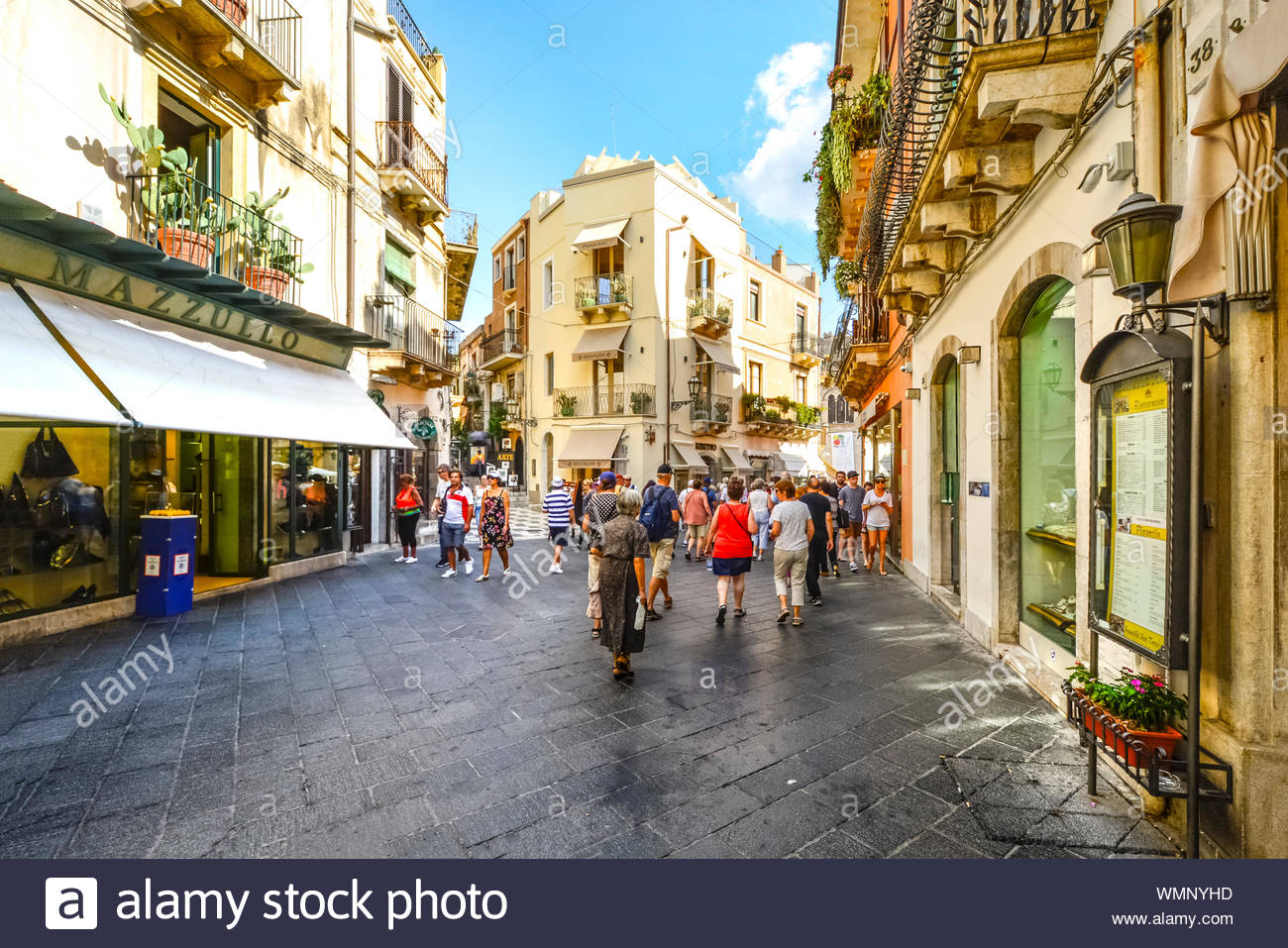 Tourists shop and wander the Corso Umberto main street in the coastal resort city of Taormina Italy on the Italian Mediterranean Stock Photo