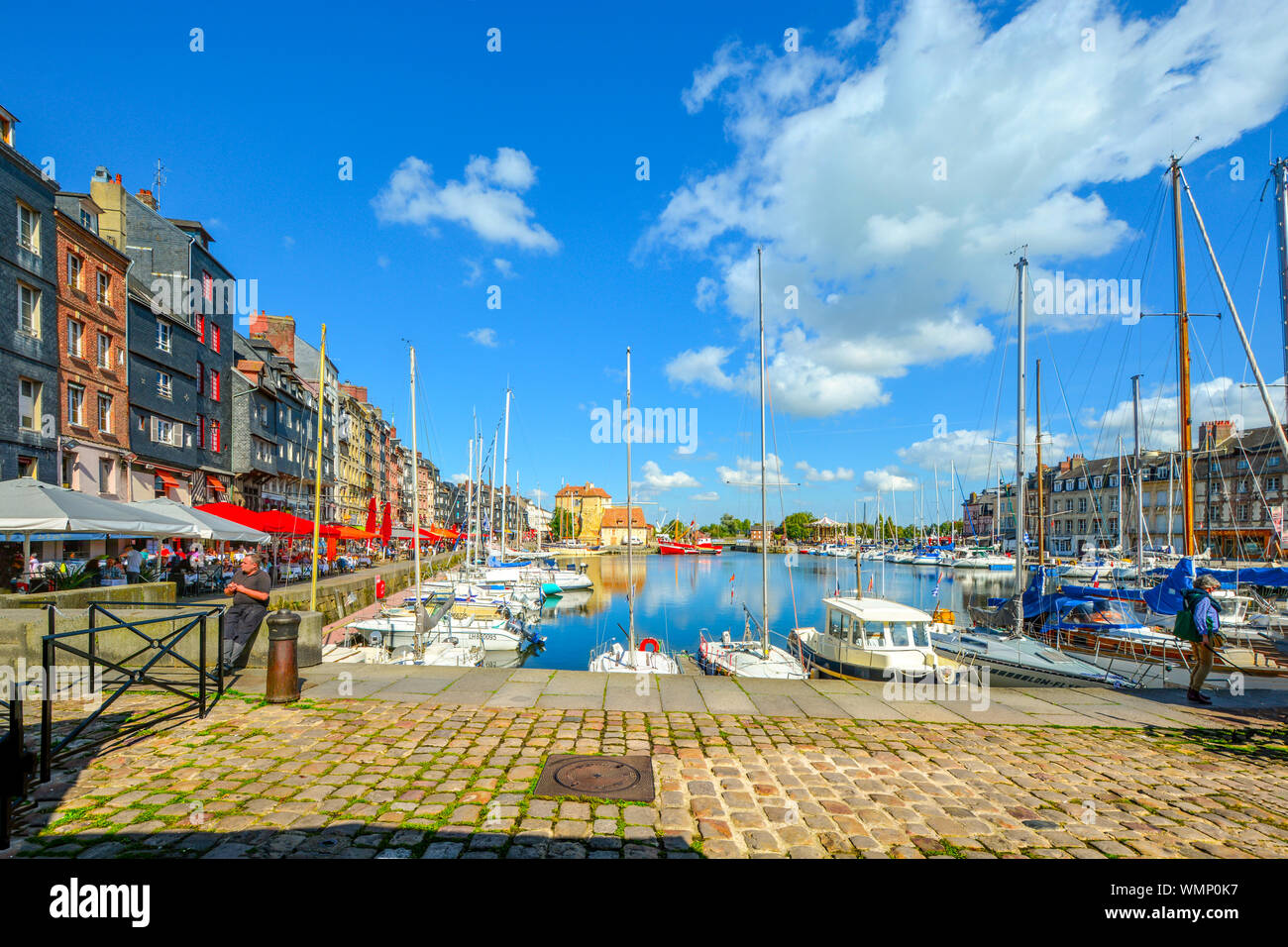 The picturesque fishing village on the Normandy coast of France, Honfleur, with boats in the harbour and tourists enjoying the sidewalk cafes Stock Photo