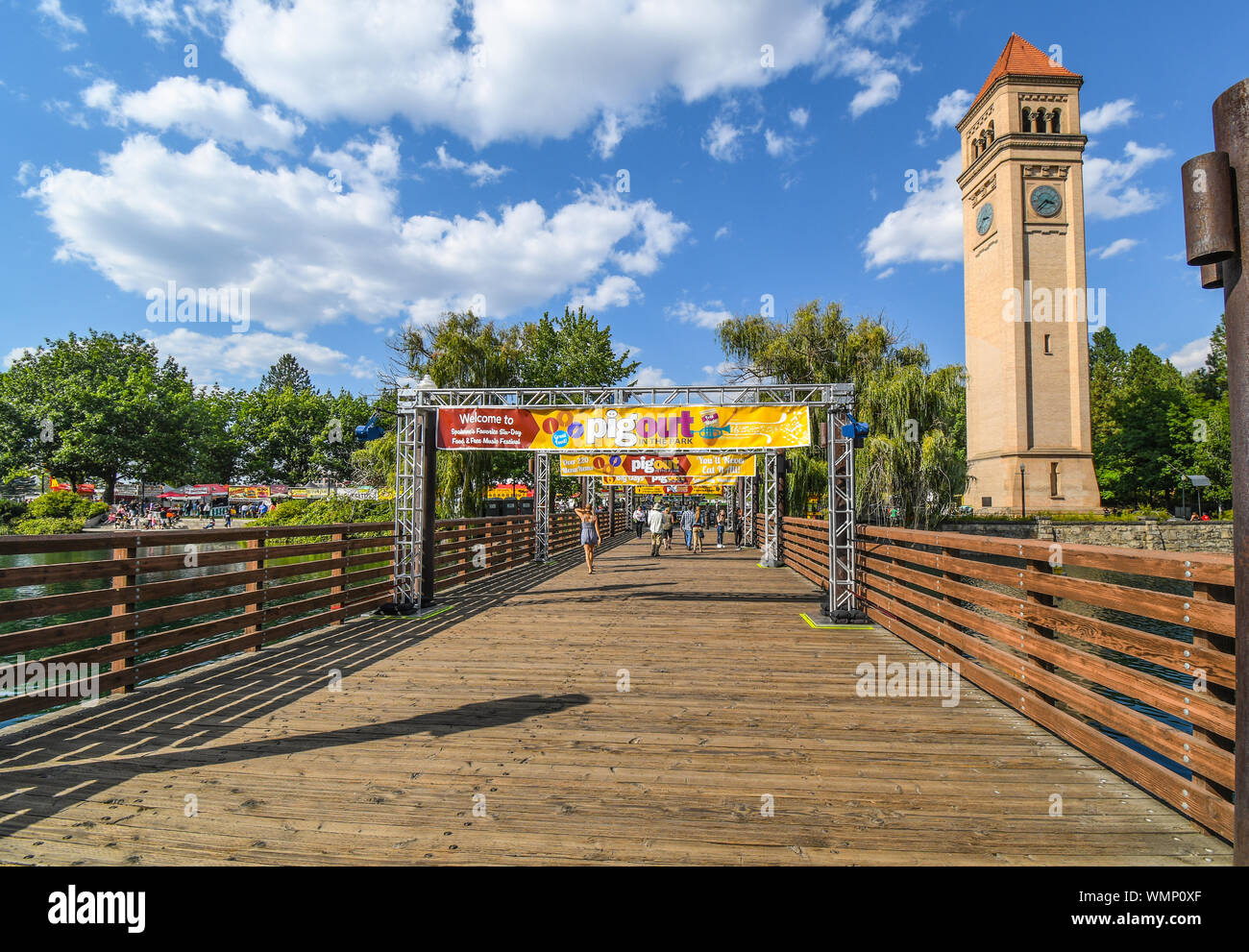Visitors cross the bridge over the Spokane River near the clock tower at the annual Pig out in the Park festival in downtown Spokane Washington Stock Photo