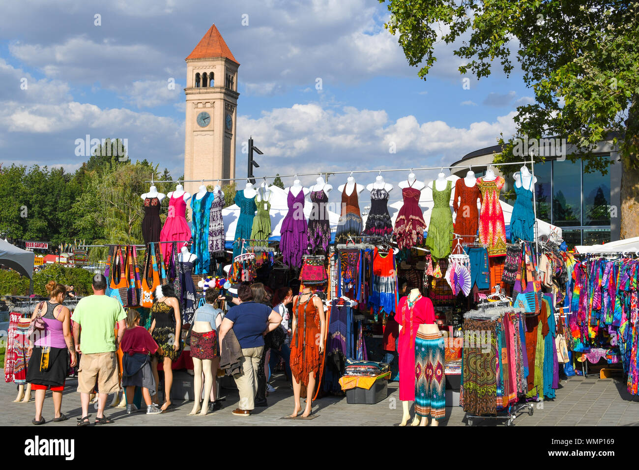 Visitors to the annual Pig Out in the Park stop at an outdoor vendor booth selling colorful dresses and clothing in Spokane Washington Stock Photo