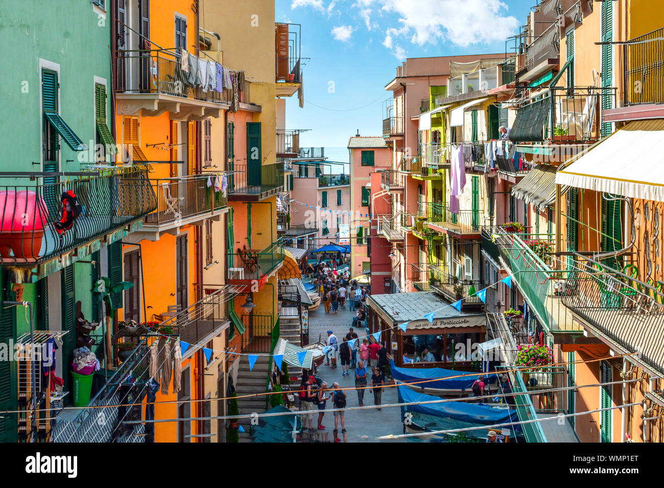 The colorful hillside village of Riomaggiore Italy, part of the Cinque Terre coast of the Ligurian Sea, with tourists enjoying it's busy main street Stock Photo