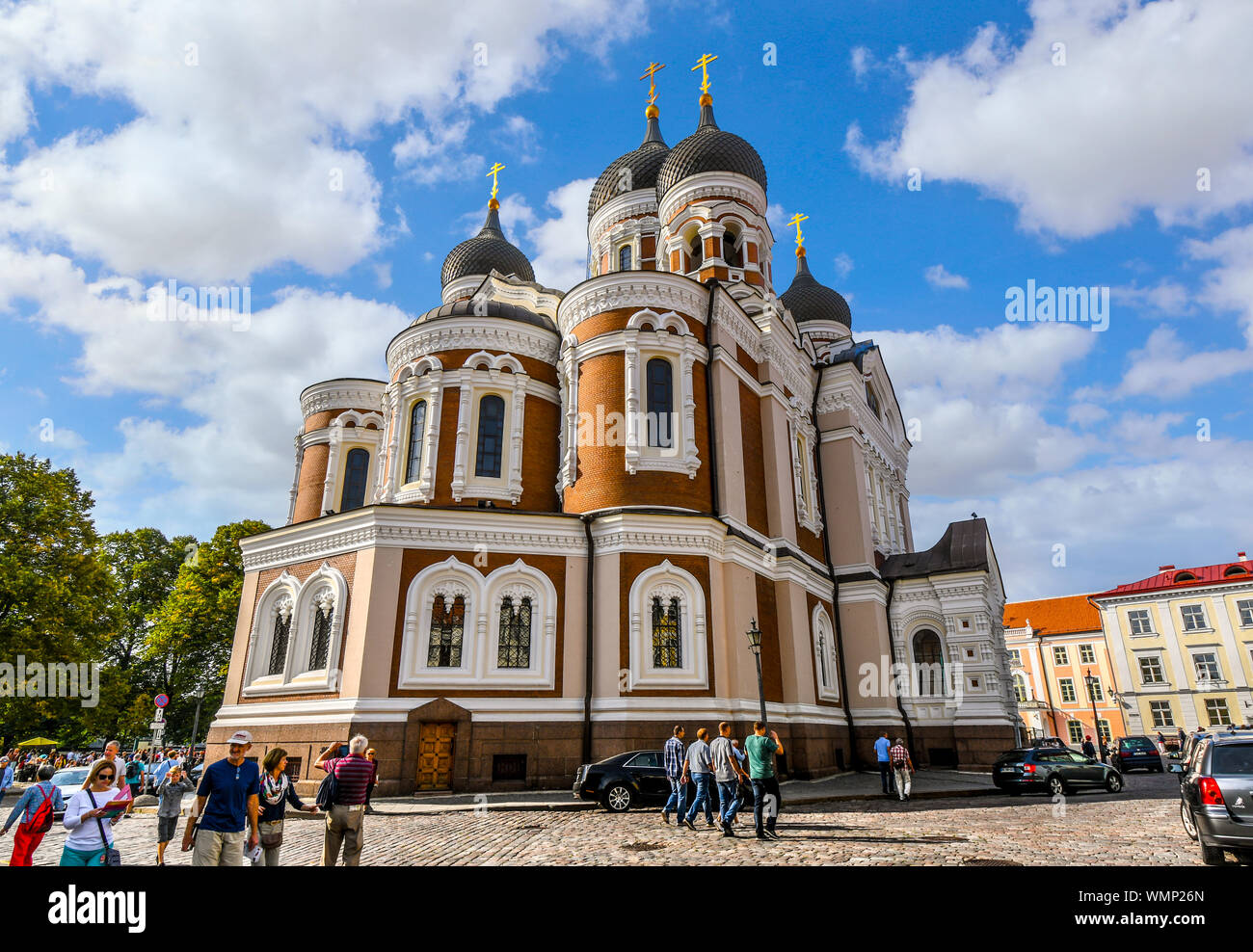 Tourists walk past the Alexander Nevsky  Church in the medieval upper town of Toompea Hill early morning in the Baltic city of Tallinn, Estonia. Stock Photo