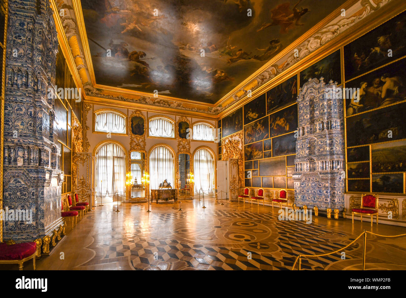 An ornate golden interior ballroom picture hall with inside the Rococo Catherine Palace near St. Petersburg, Russia. Stock Photo