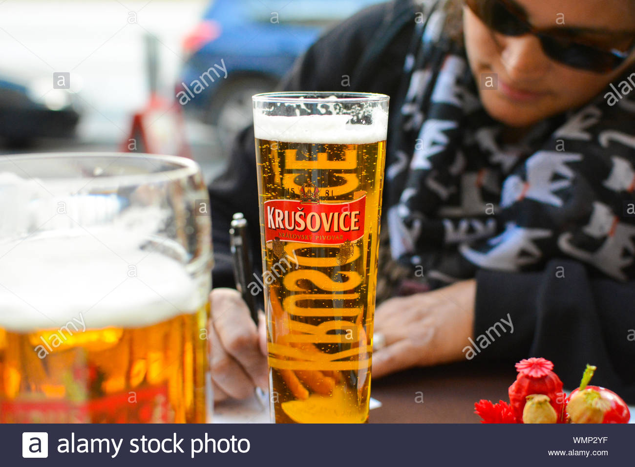 A woman wearing dark glasses and drinking a beer fills out postcards at a sidewalk cafe Stock Photo