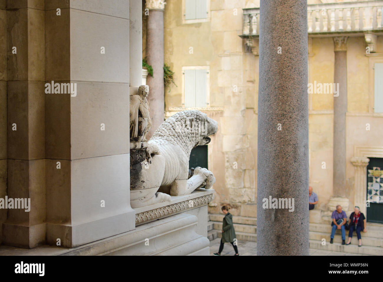 A lion statue outside the Cathedral of Split facing the Peristyle of Diocletian's Palace in Split Croatia as tourists enjoy the afternoon Stock Photo