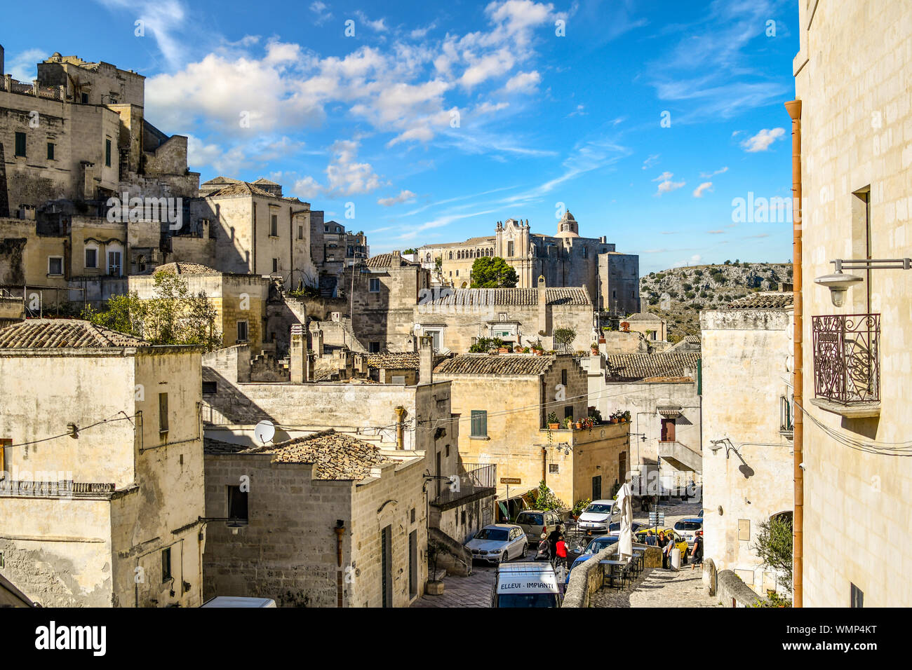 Typical street running through the ancient sassi town of Matera, Italy, with the Convent of Saint Agostino in the distance. Stock Photo