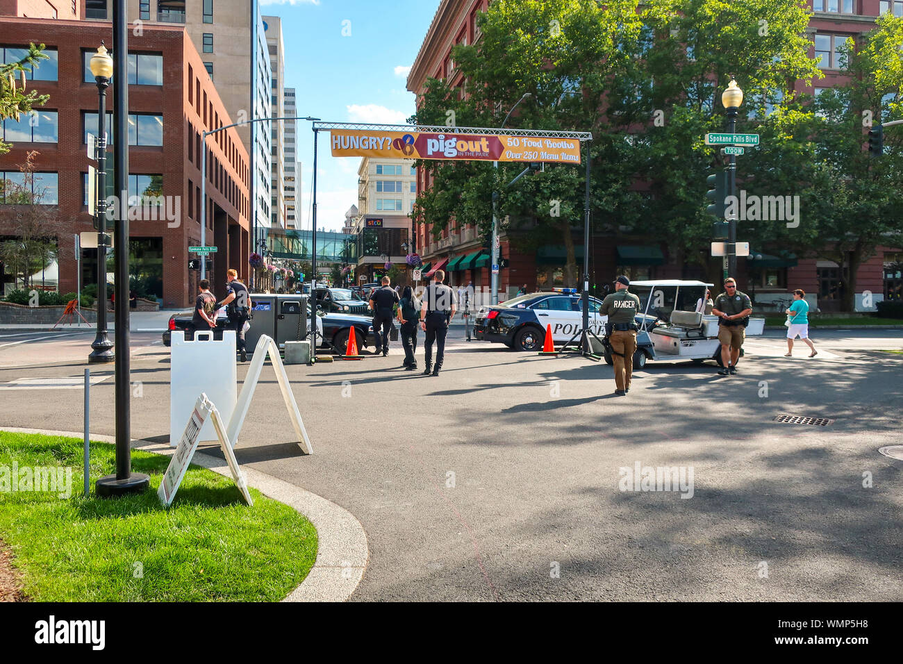 Local police and ranger officers escort a handcuffed suspect through Riverfront Park in the downtown area of Spokane, Washington. Stock Photo