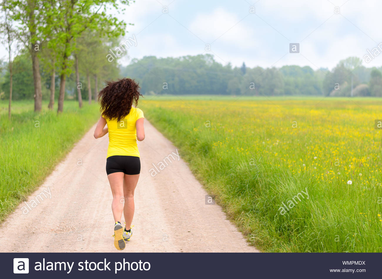 Fit muscular young woman jogging in farmland along a dirt track between lush green fields in a healthy lifestyle concept Stock Photo