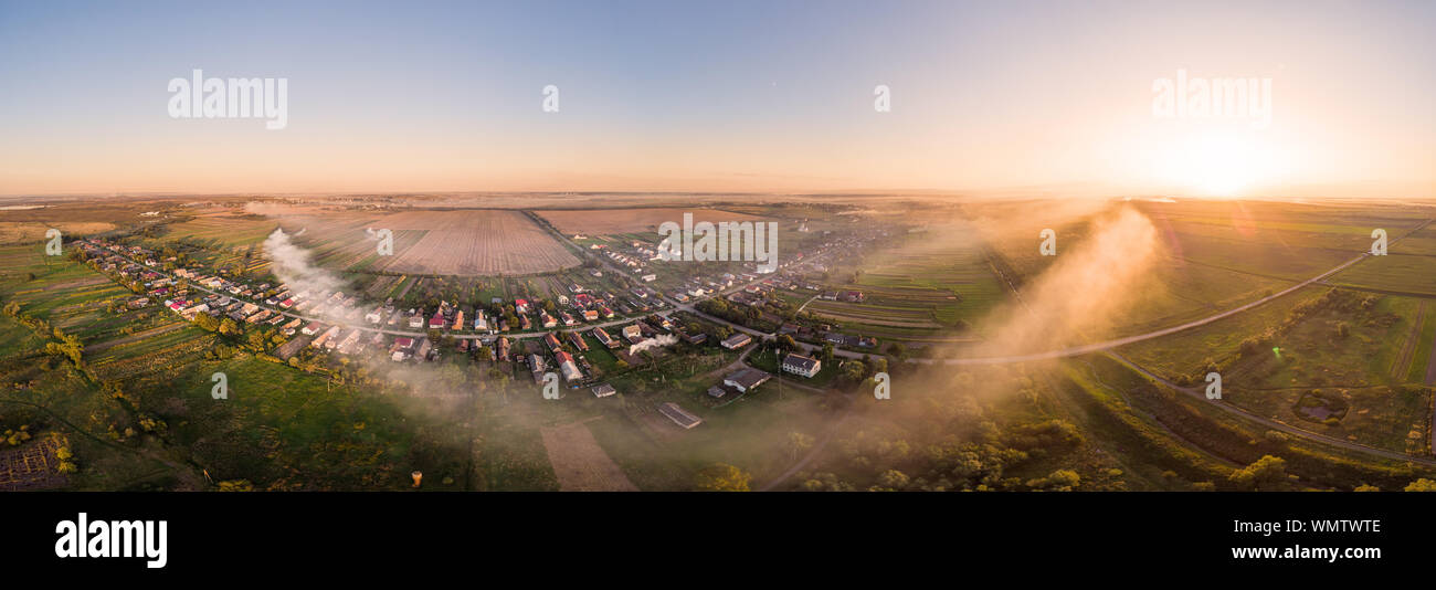 Aerial view of traditional Ukrainian village at sunset. Wide angle panoramic landscape of rural area. Early autumn. Smoke spreads through the village. Stock Photo