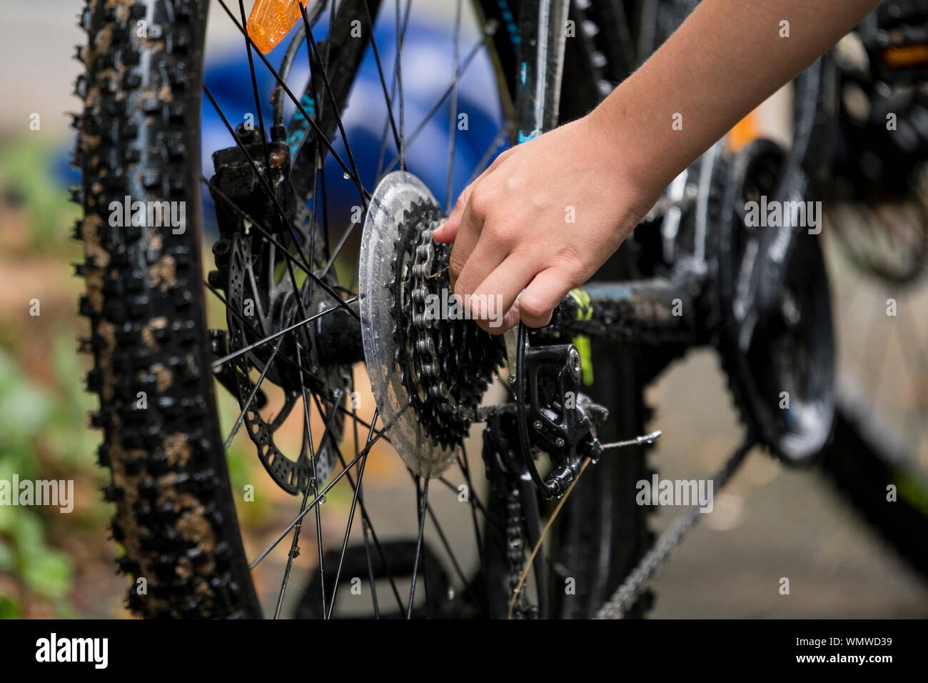 Child repairs and cleans his bike with water Stock Photo