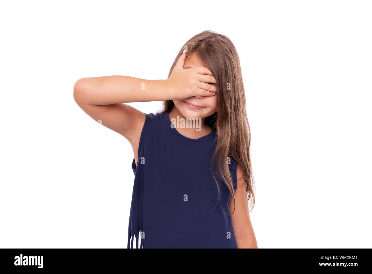 Little girl closed her eyes with her hand. Stock Photo