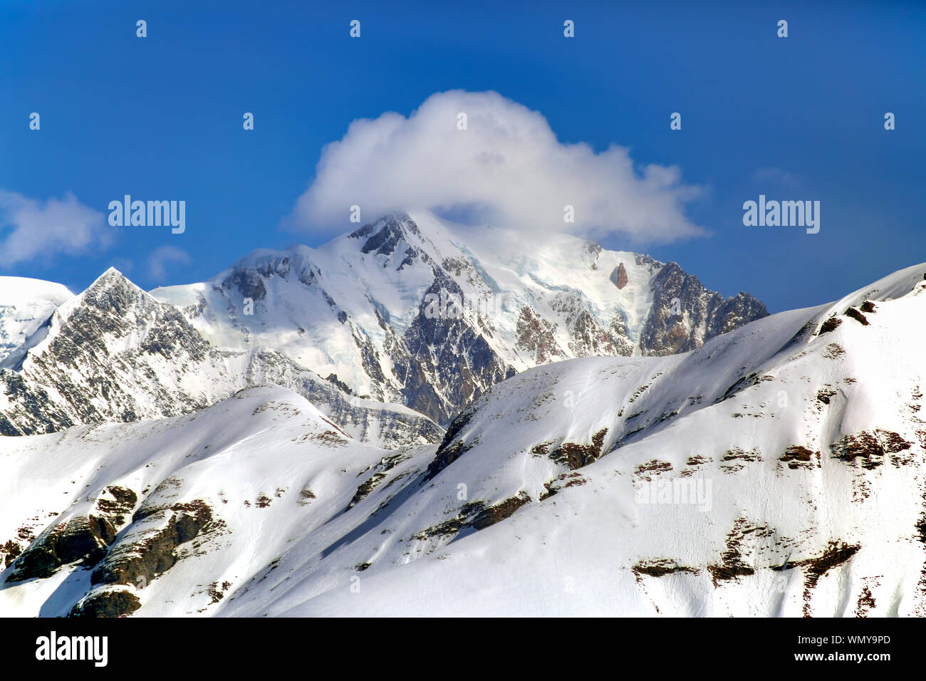 Clouds around the peak of Mont Blanc (highest of Europe) at French Alps on a sunny day (View from Rochebrune). Stock Photo