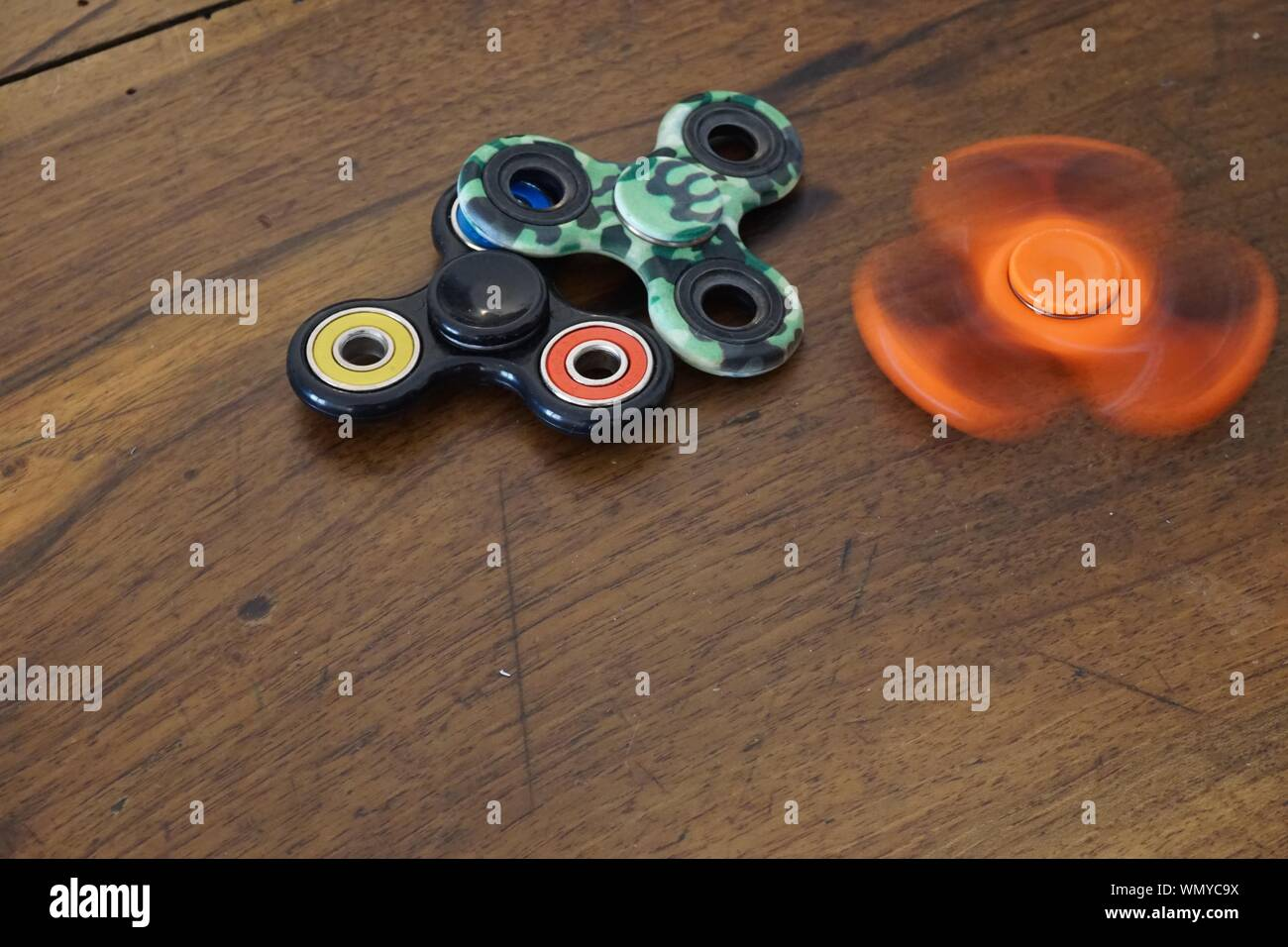 High Angle View Of Colorful Fidget Spinners On Wooden Table Stock Photo