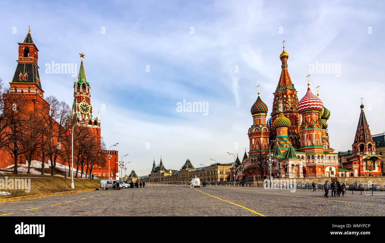 Moscow, Russia, April 2013 Tourists visiting St Basils Cathedral, Beautiful Spasskaya Tower and The Tsars Tower on the Red Square at beautiful sunrise Stock Photo