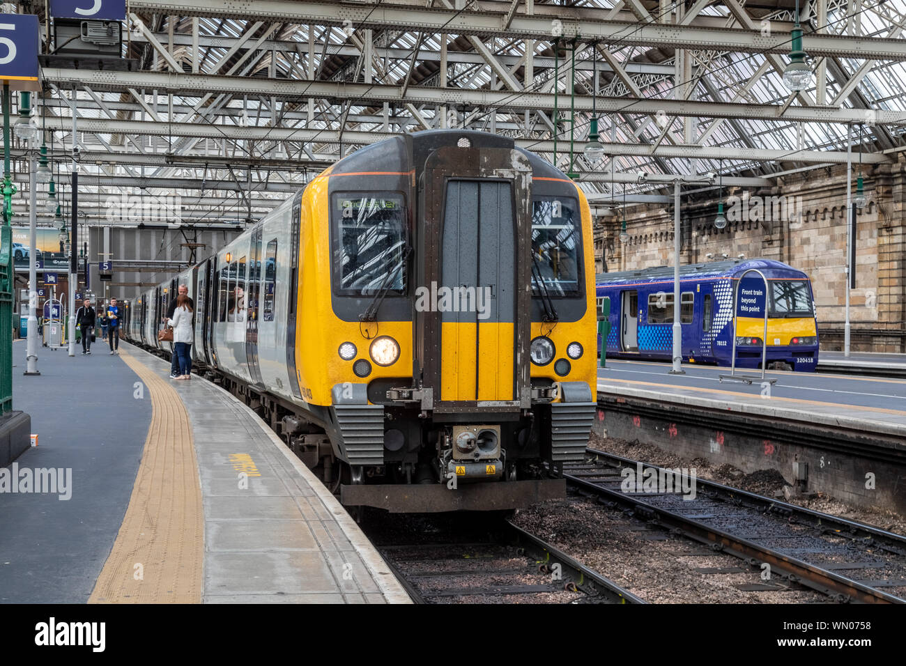 A First Transpennine Class 350 electric train at platform 5 of Glasgow Central. This train is operating a service to Manchester Airport Stock Photo