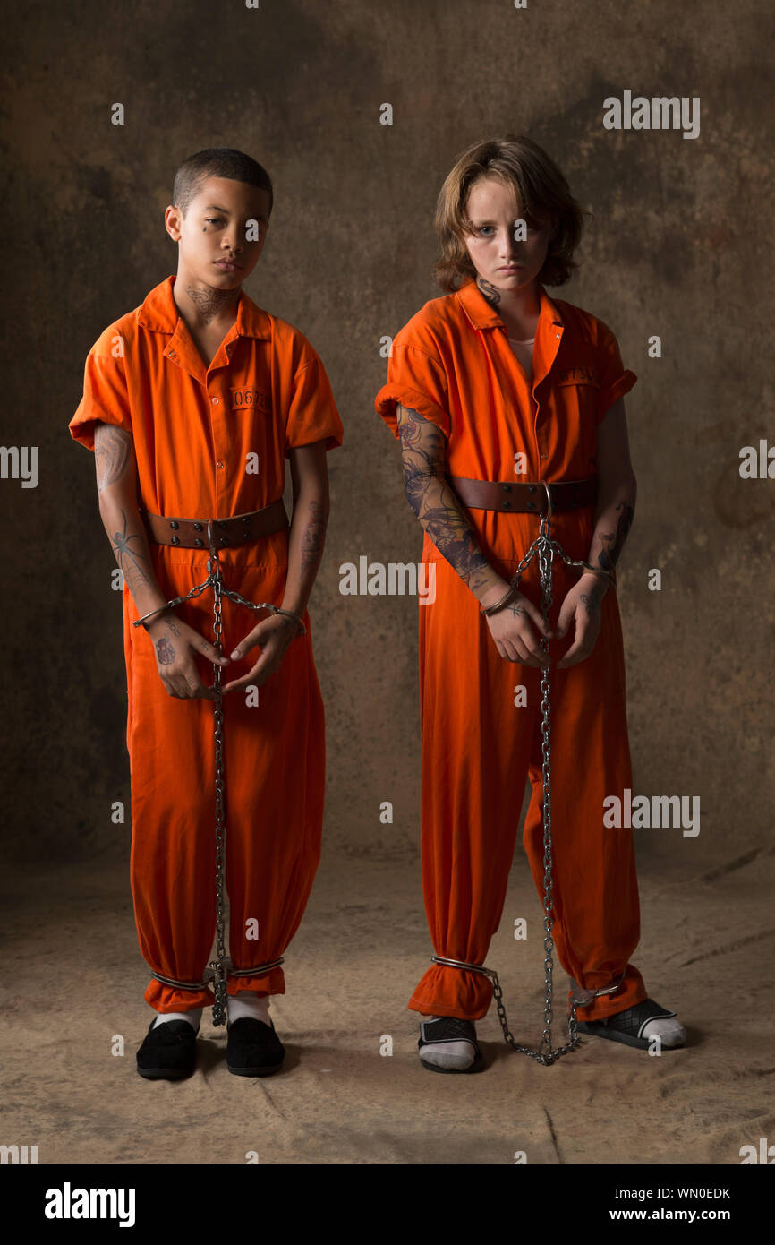 Boys in prisoner jumpsuits and handcuffs Stock Photo - Alamy