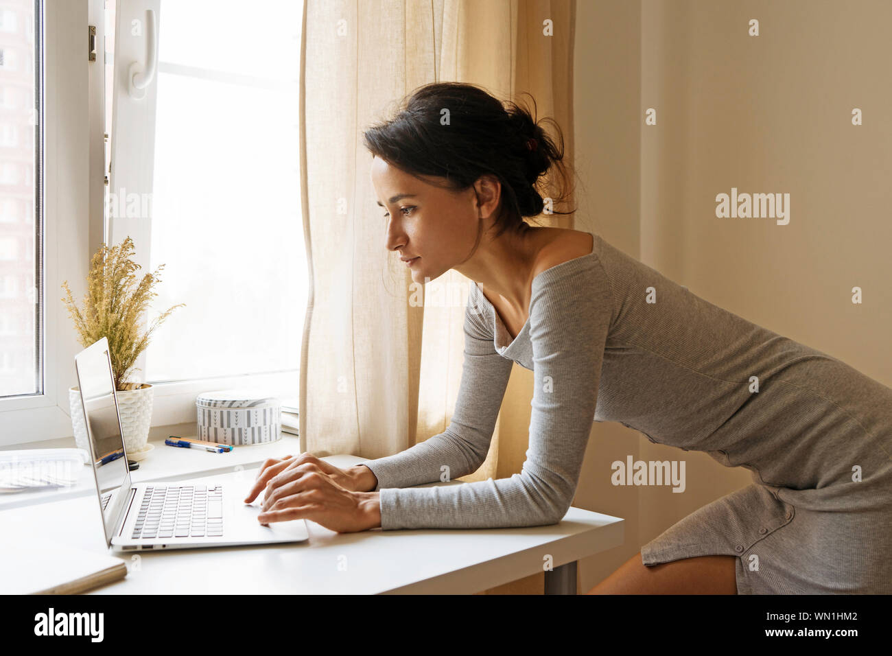 Woman Leaning On Table Using Laptop Stock Photo Alamy