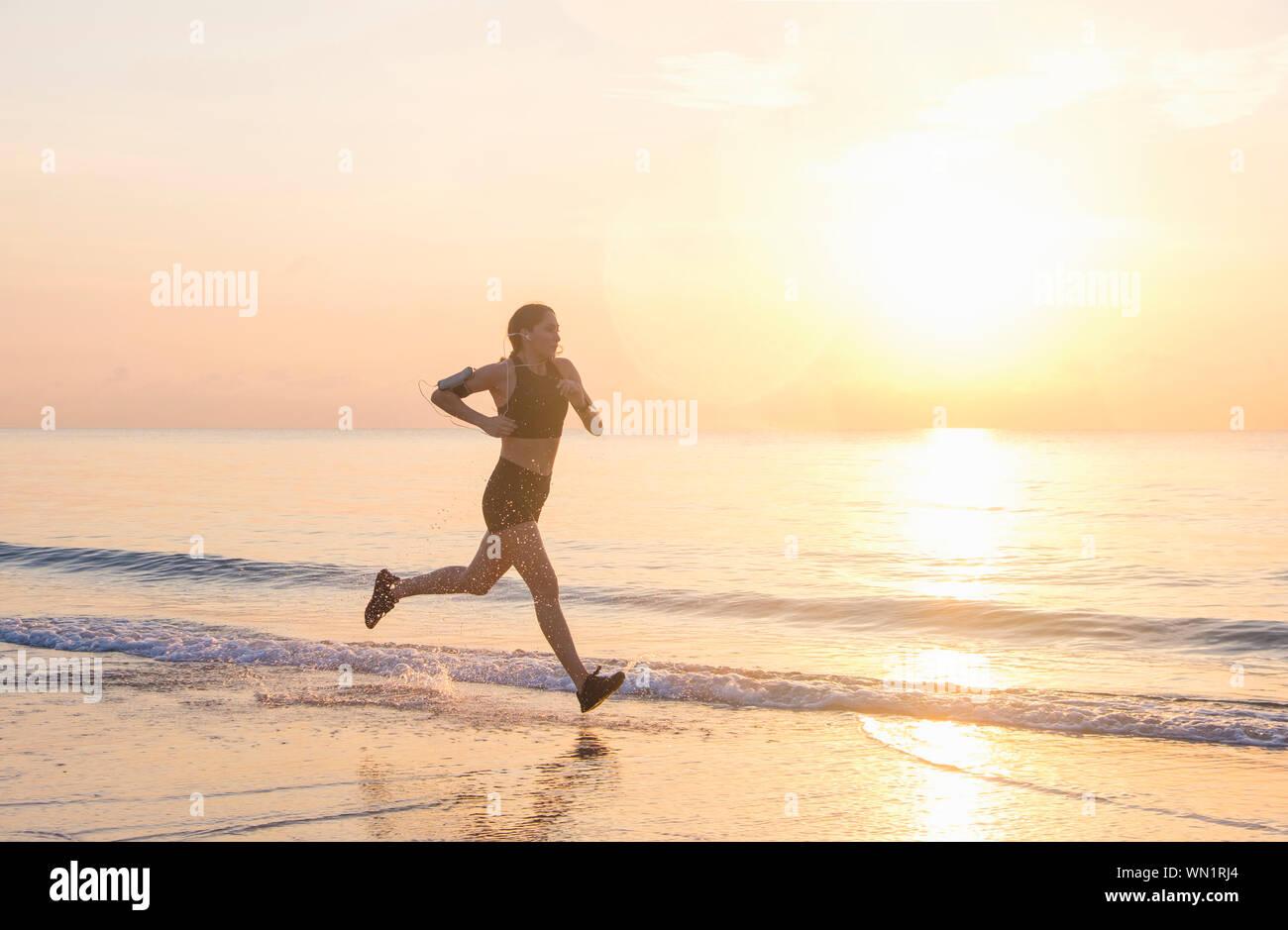 Woman jogging on beach at sunset Stock Photo