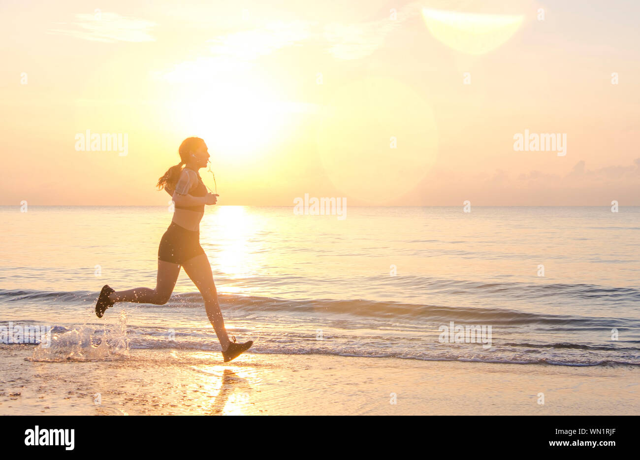 Woman jogging on beach at sunset Stock Photo