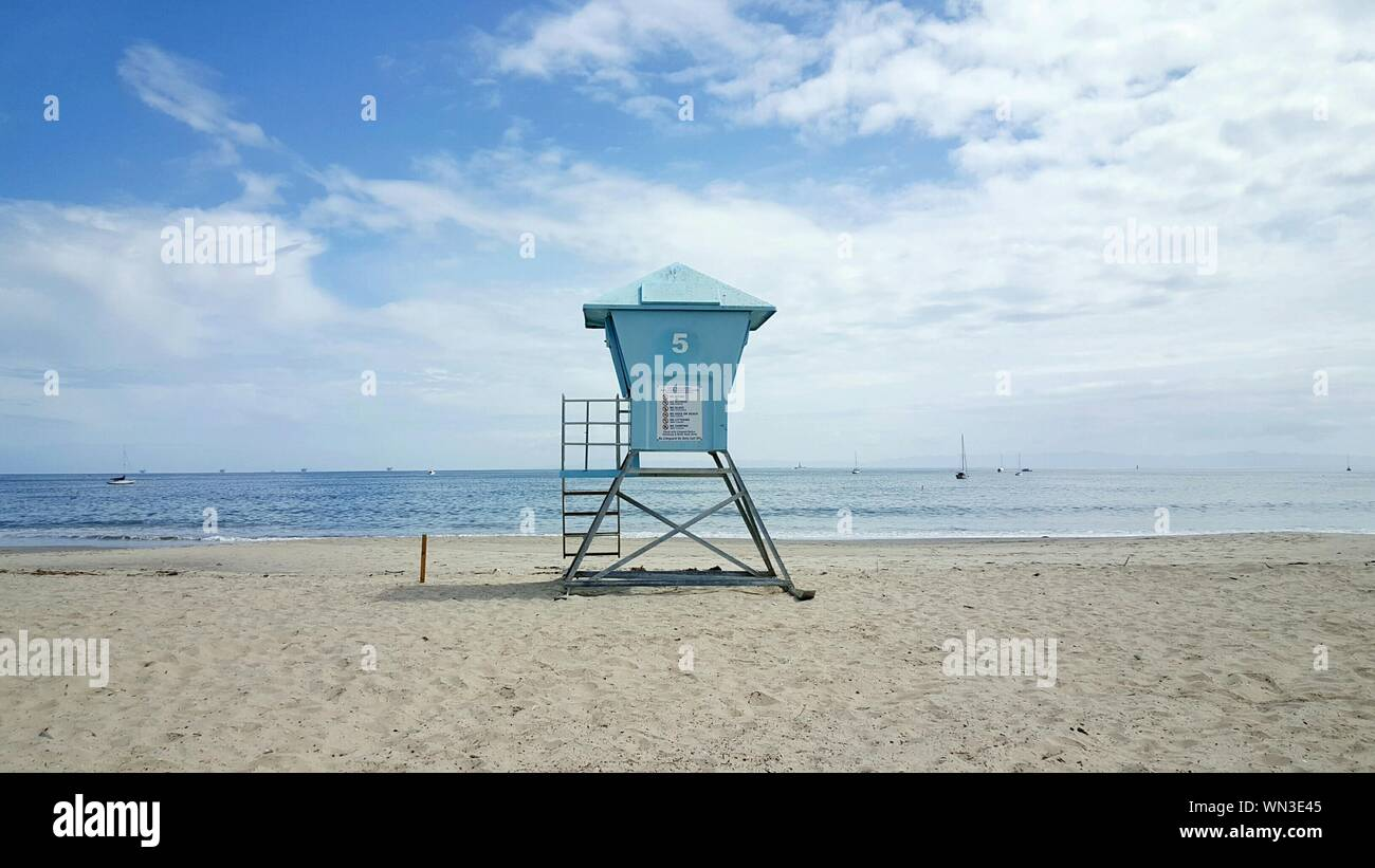 Scenic View Of Lookout Tower On Beach Against Cloudy Sky Stock Photo